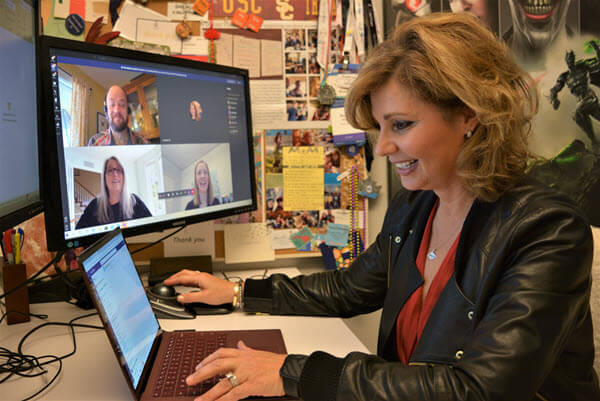 Kaufman sits at her desk during a Microsoft Teams call and smiles at her laptop.