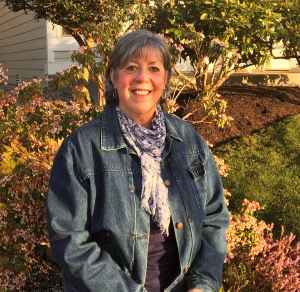 Susan Sims stands in her yard and smiles at the camera.