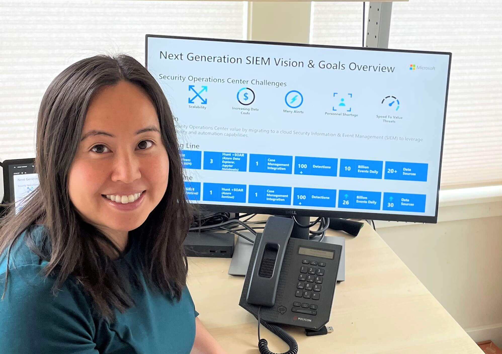 Lau sits at a desk with the vision and goals of a new SIEM on the screen.