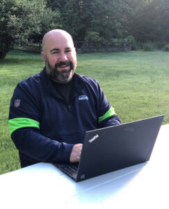 Gagnon sits at a table with his laptop and smiles for the camera.