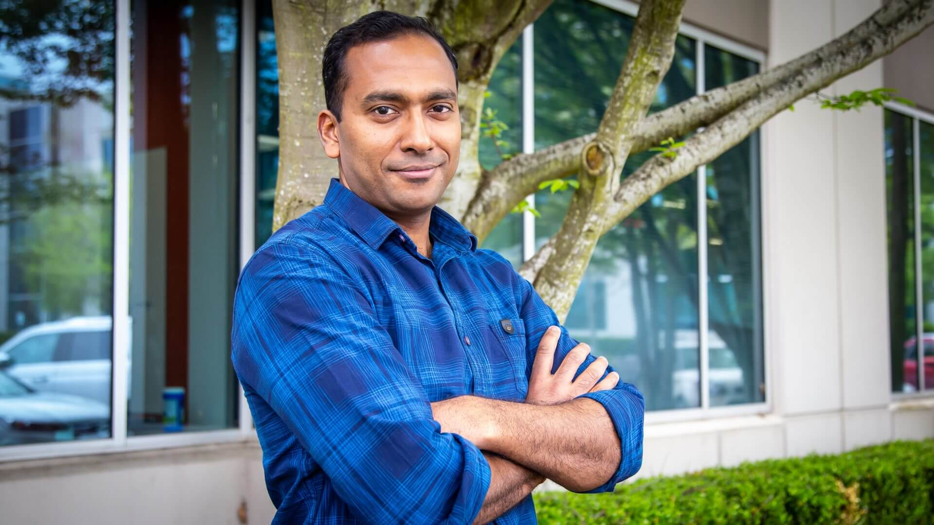 Garg stands in front of a large tree and building with his arms crossed, and he smiles at the camera.
