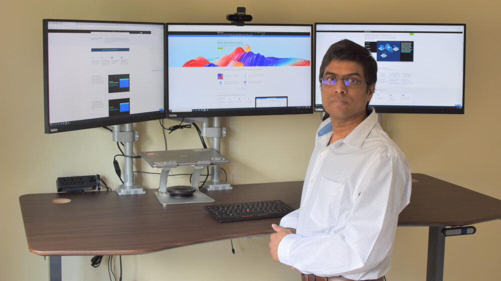 Jayapalan stands in front of his three-monitor workstation in his office.