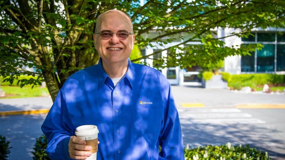 Apple holds a cup of tea as he smiles standing in front of a tree outside a Microsoft office.