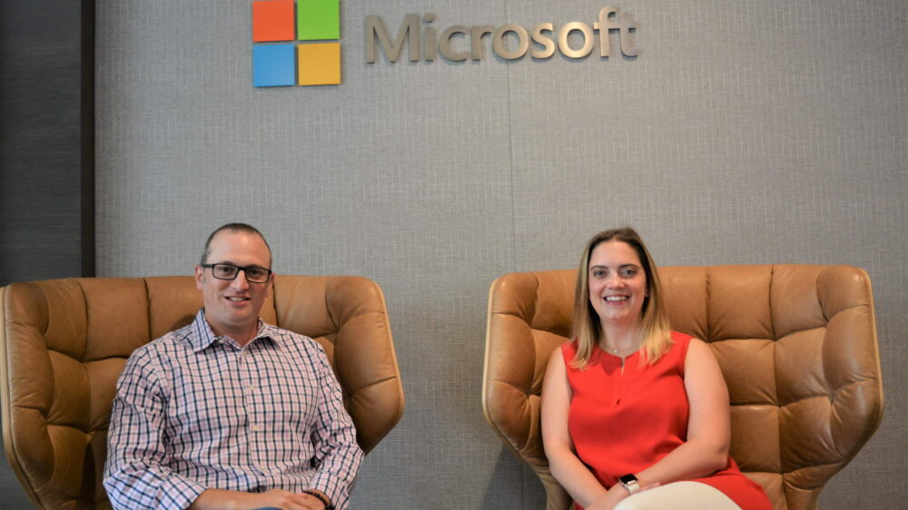 Yedinak and Laves sit and smile below a Microsoft logo inside a Microsoft building.