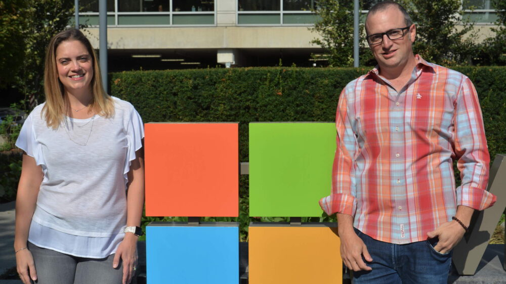 Yedinak and Laves stand and smile on either side of a Microsoft logo outside a Microsoft building.
