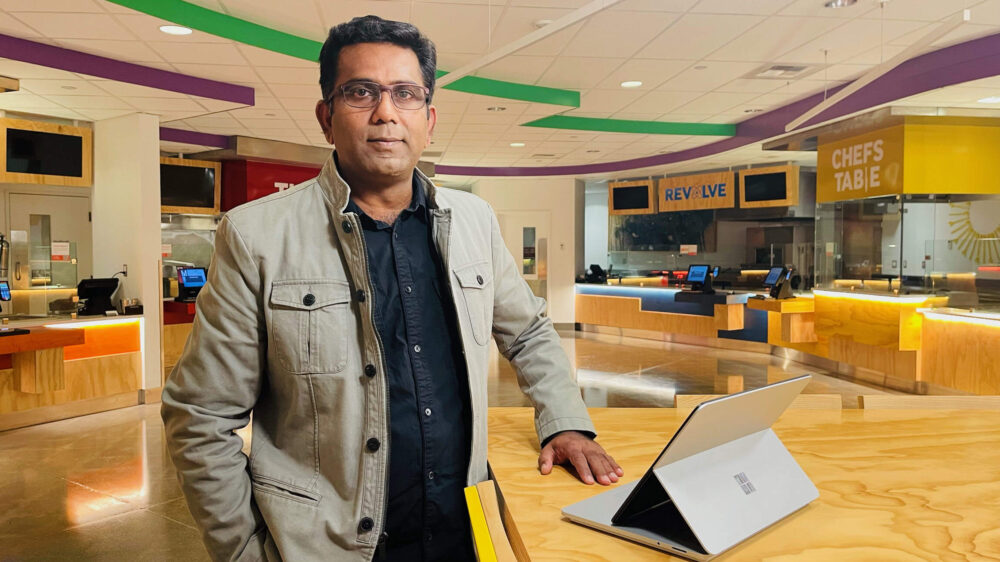 Selvaraj poses for a photo with his Microsoft Surface at a table in a Microsoft café.