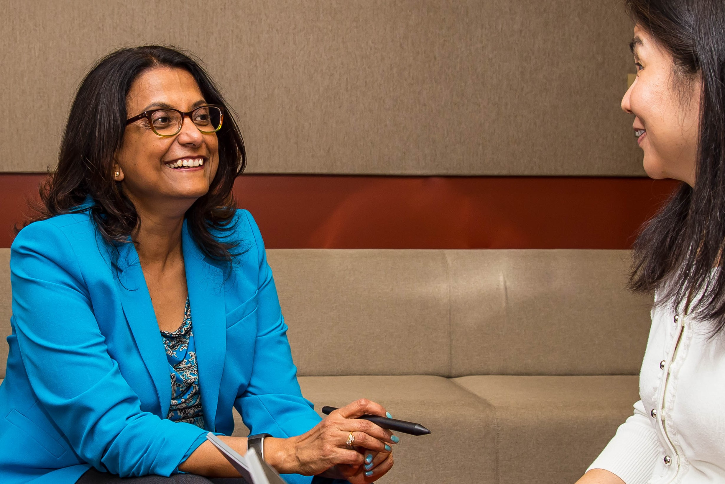 Sarmila Basu talks with one of her team members in a meeting room at Microsoft