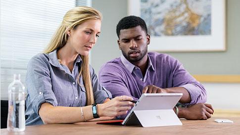 Donna e uomo in sala riunioni, protesi verso il monitor di un Surface Pro 4