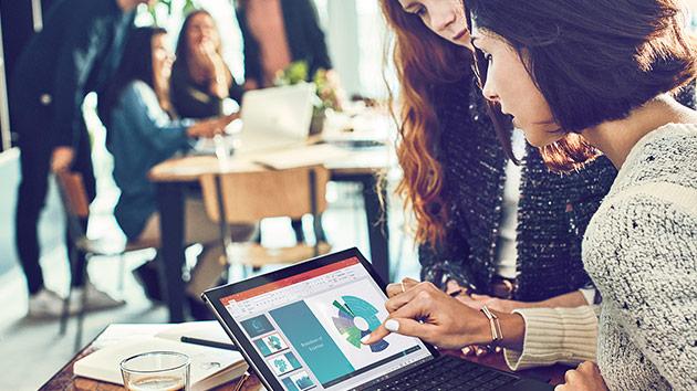Due professionisti che interagiscono con Surface Pro