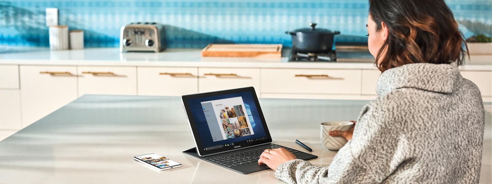 女性がキッチンカウンターに座って、携帯電話でWindows 10ラップトップコンピュータを使用