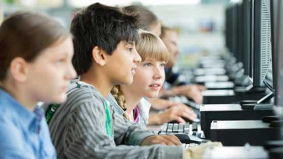 教室でコンピューターを利用する子供たち