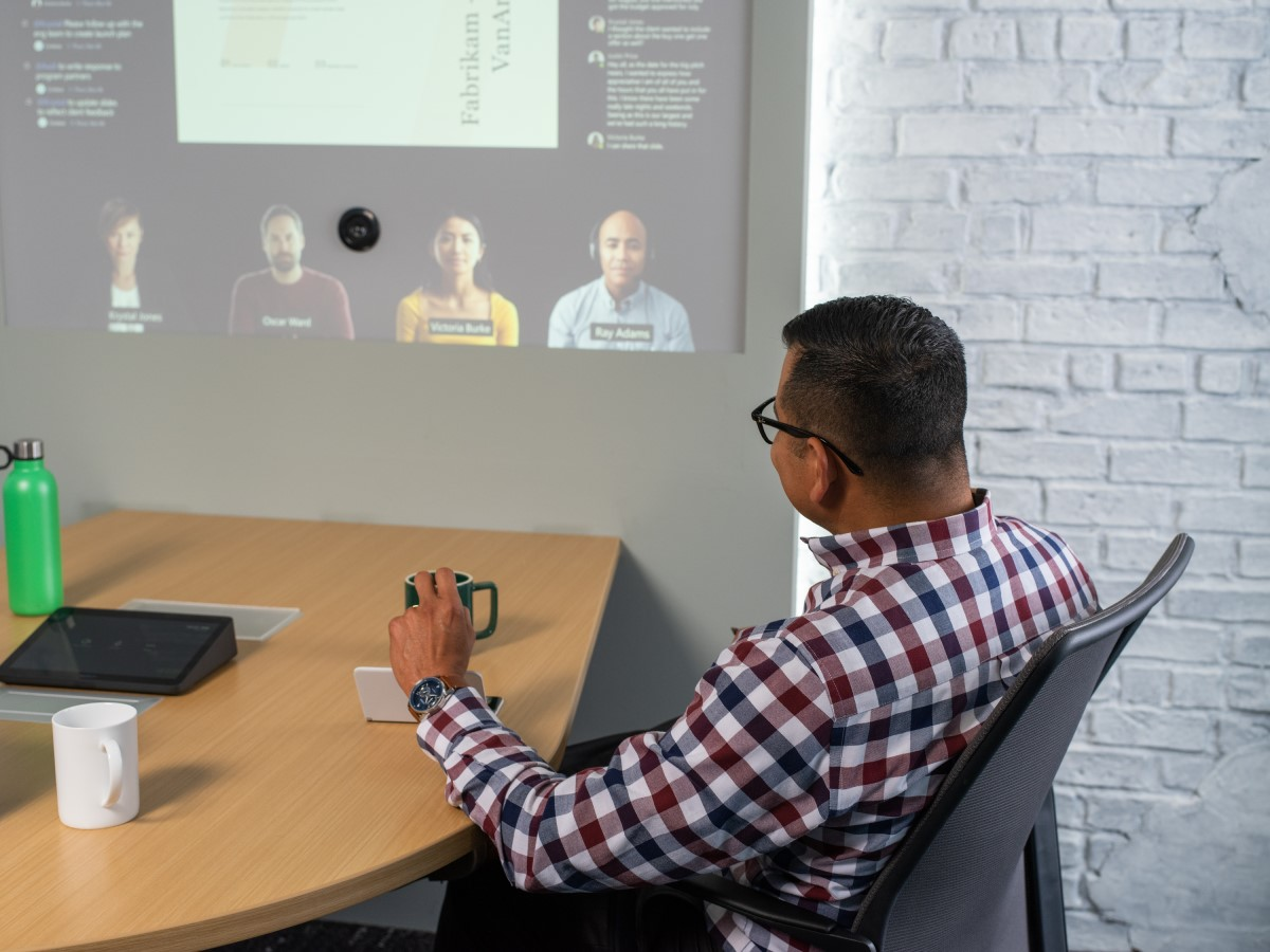 Image for: Adult male sitting at conference table looking at screen projected on wall.