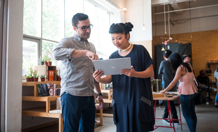Image of two coworkers looking at a tablet.