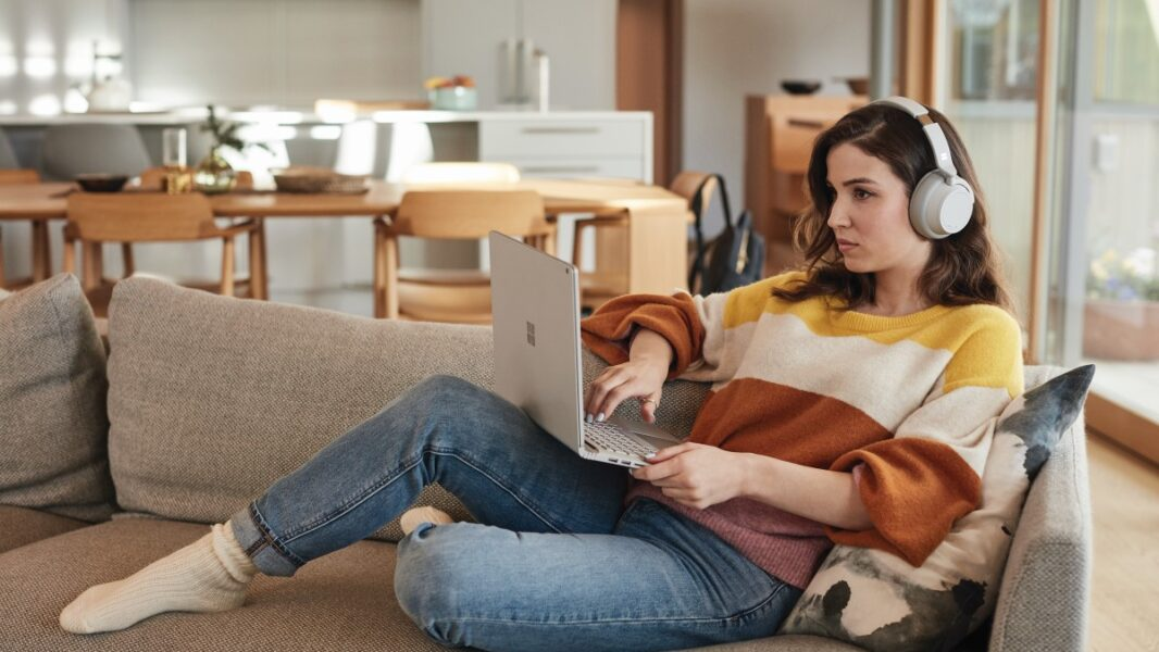 Female student with Surface Book 2 and Surface Headphones at home works remotely or attends Teams meeting.