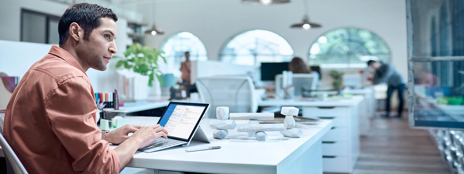 Surface Pro 4, stor skjerm og tastatur på et skrivebord.