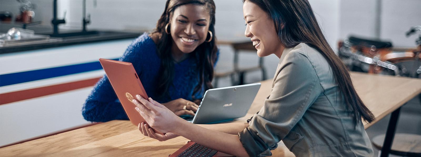To kvinner sitter ved et bord og ser på en nettbrettskjerm som holdes opp mellom dem av en annen kvinne