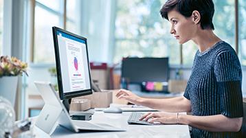 Vrouw die Surface Studio aan haar bureau gebruikt.
