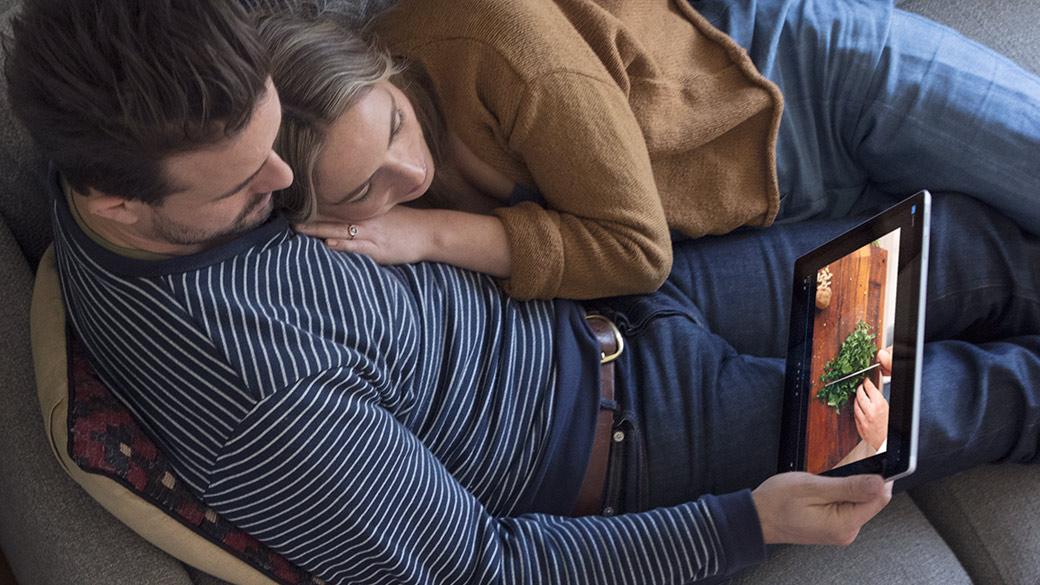 Man en vrouw samen in de lounge terwijl ze aan het werk zijn met een Surface Pro