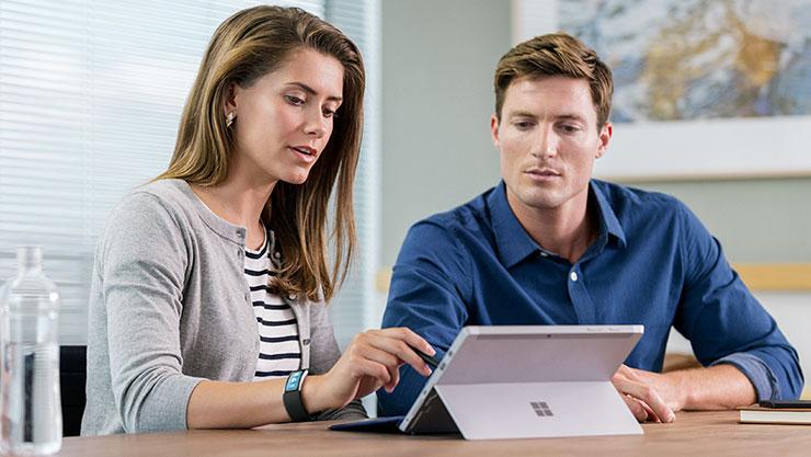Twee vrouwen kijkend naar een Surface Book