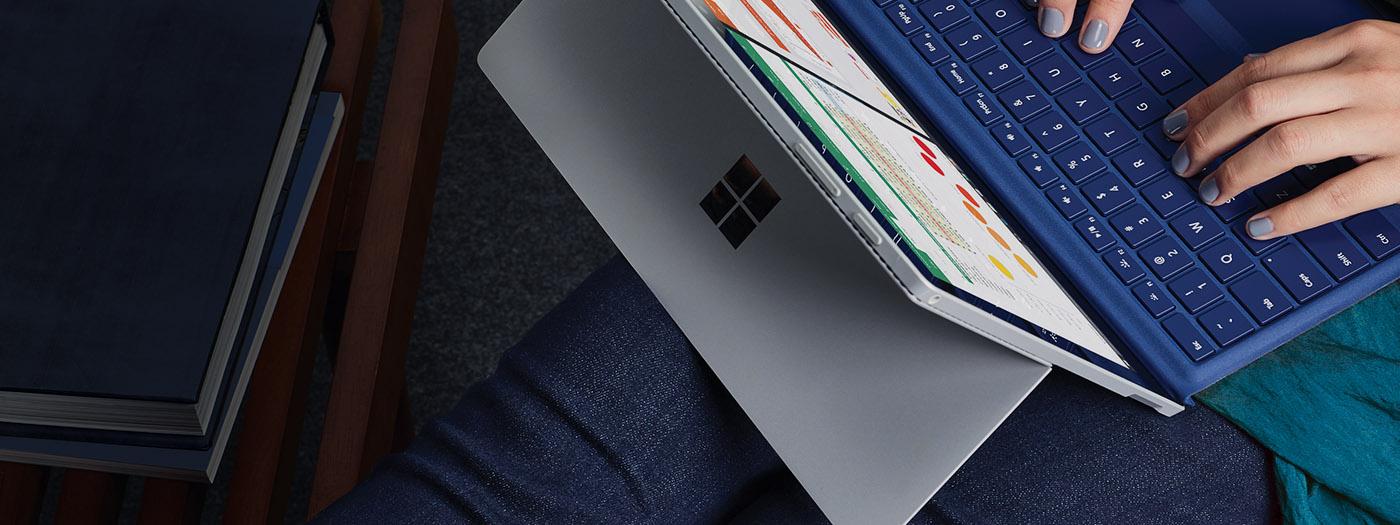 Bovenaanzicht van iemand die met een laptop op schoot zit