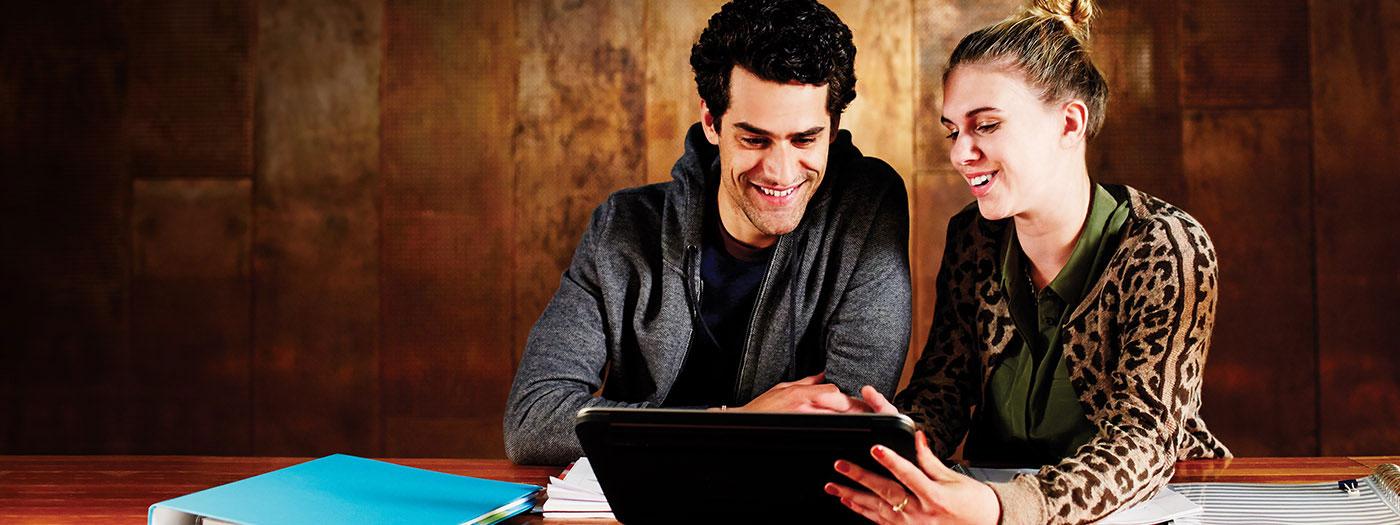 Twee studenten wijzen naar een laptop