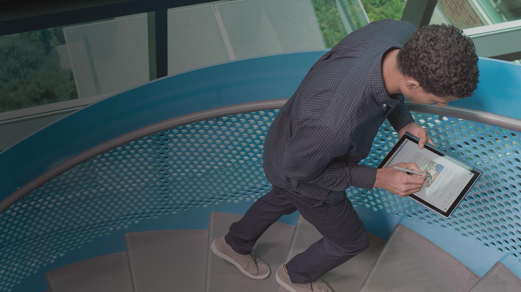 Tableten dolgozó férfi megy fel egy lépcsőn