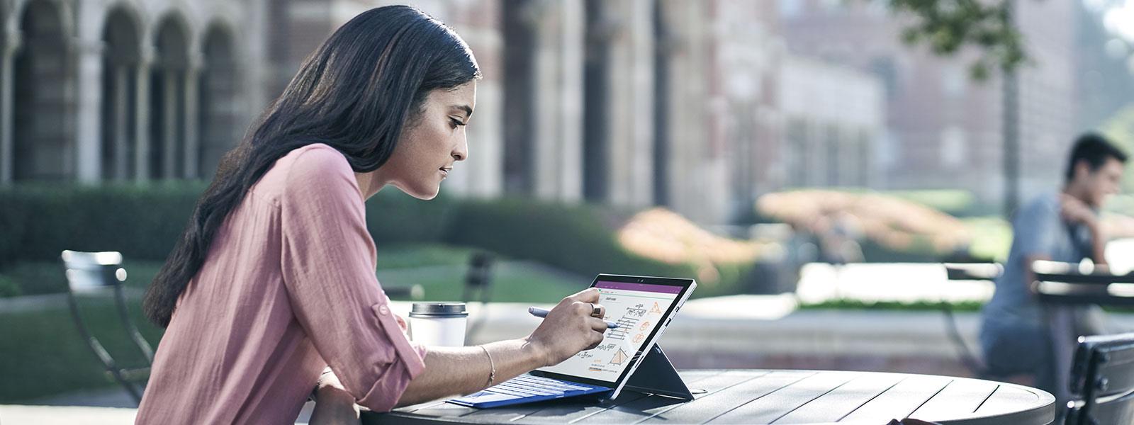 Kobieta rysująca na ekranie Surface Studio piórem Surface i powiększająca obraz dwoma palcami drugiej dłoni.