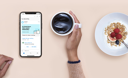 Image for: Cortana Daily Briefings on a mobile device. User holds a cup of coffee. Next to the coffee is a breakfast dish.