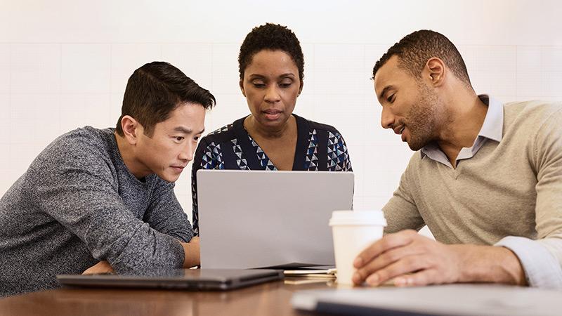 Equipe colaborando em um laptop