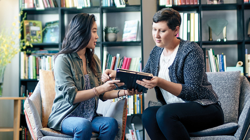 duas mulheres compartilhando um tablet