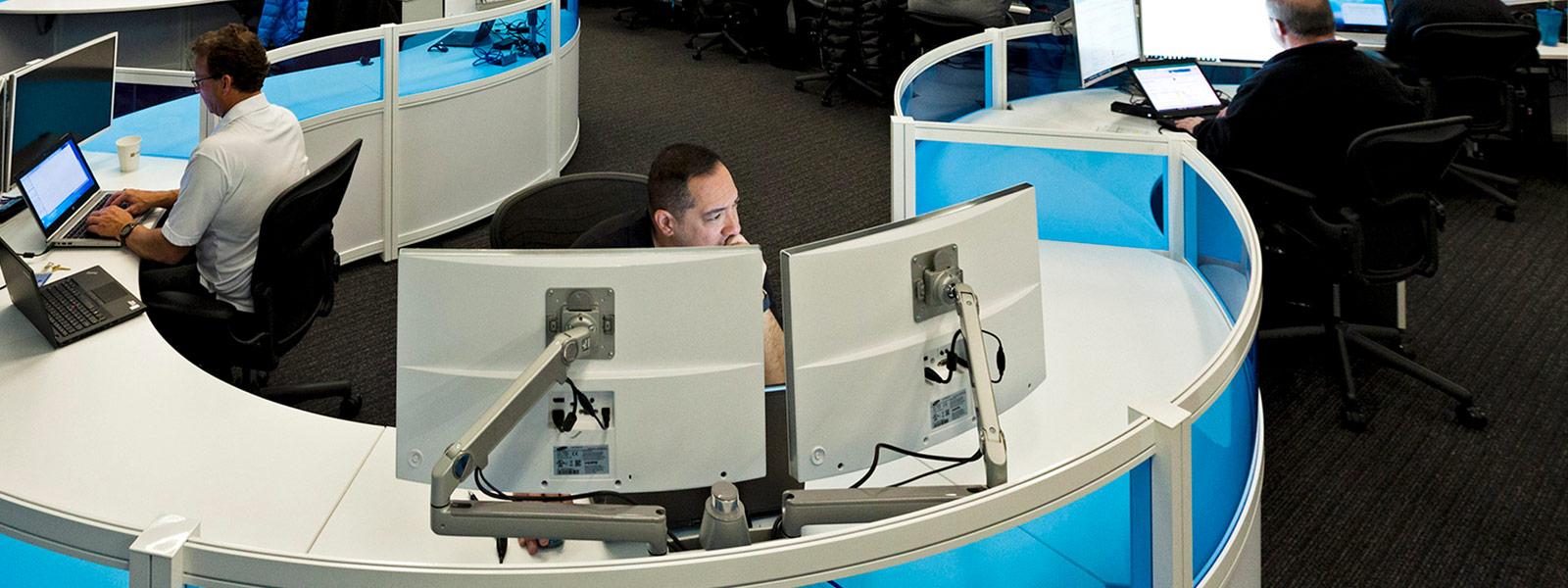 Homem no centro de segurança cibernética olhando para 2 monitores
