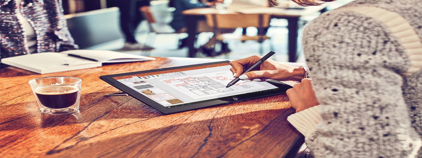 Mulher usando um stylus em um dispositivo em um café