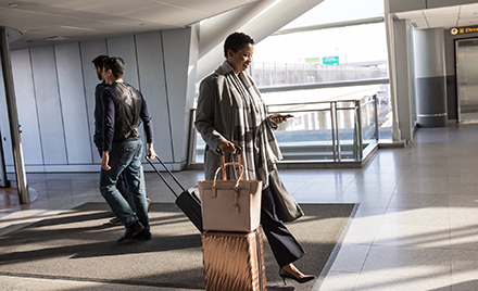 Image for: Image of an enterprise female in business travel at airport.