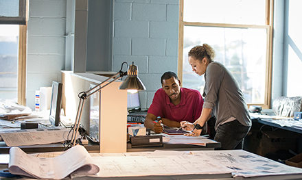 Two coworkers collaborate over a document on a desk.
