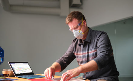 Image for: Manufacturing business owner wearing a mask and reviewing schedule in Shifts within Microsoft Teams.