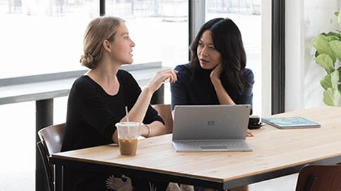 Duas mulheres sentadas num café com um Surface Book 2 em modo de visualização frente a si.