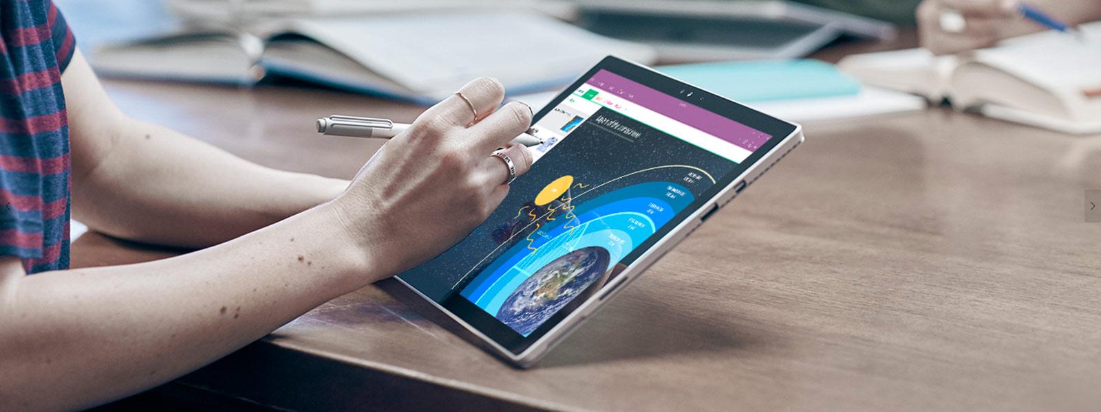 Mulher a utilizar uma Caneta para Surface no Surface Pro 4.