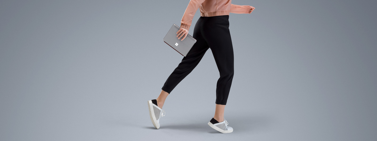 Rapariga a caminhar e a segurar num Surface Go