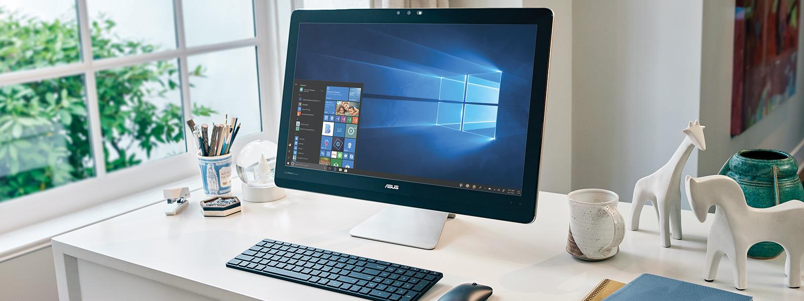 Un desktop ASUS pe un birou, cu un mouse și o tastatură wireless lângă acesta