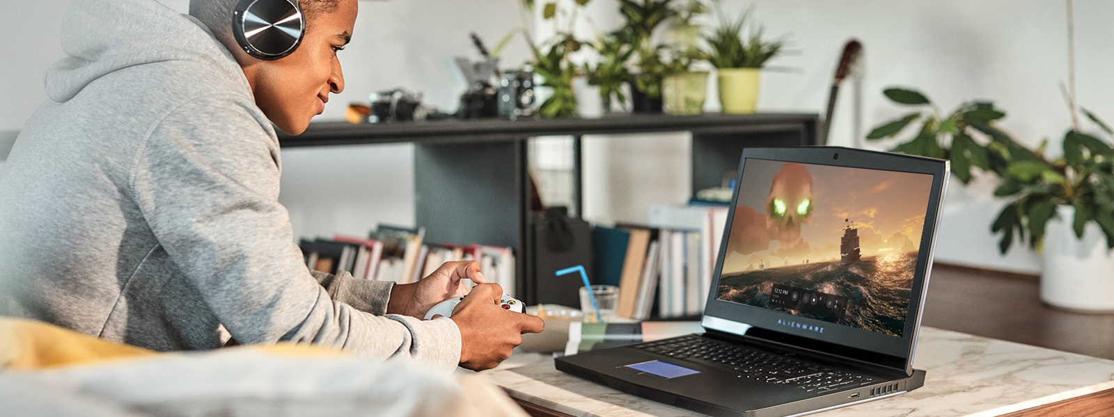 Мужчина в наушниках и с геймпадом Xbox в руках играет в игру Sea of Thieves на ноутбуке с Windows 10