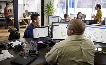 Image of an office of tech workers using Microsoft Office products.