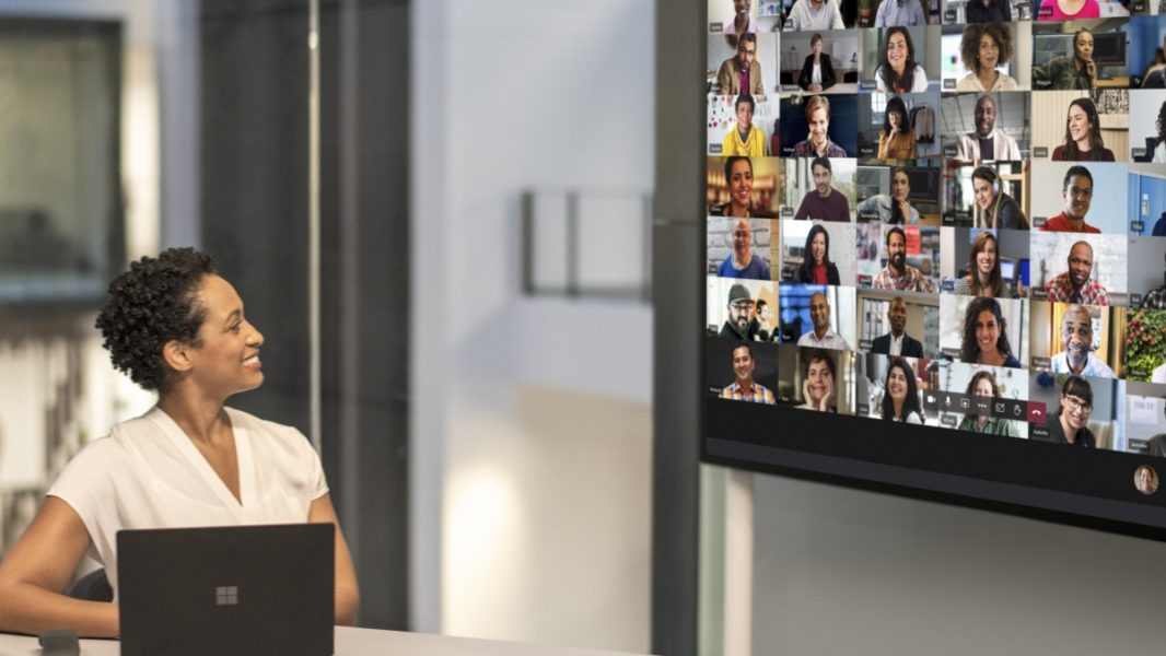 """Adult female meeting in a conference room while using Microsoft Teams Together Mode on a Surface Hub 2S 85"""" device."""