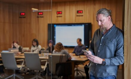 Bearded man looking at his phone with background of a blurry conference room of people working.