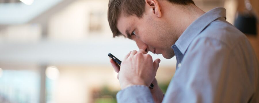 Man with low vision holds a mobile phone close to his face in order to view the screen.