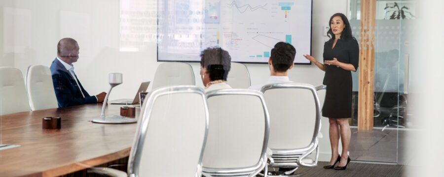 Female executive giving presentation to group in corporate office conference room.