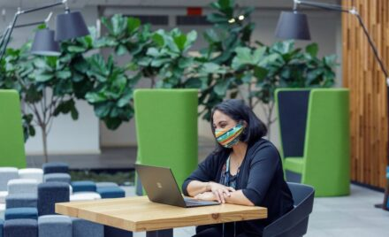 A female employee working on her Surface laptop wearing a mask and smiling.