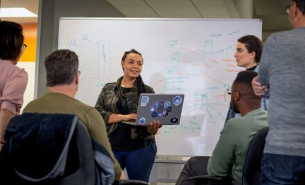 Female developer speaking in front of a white board during team stand up meeting, holding a PC laptop personalized with stickers.