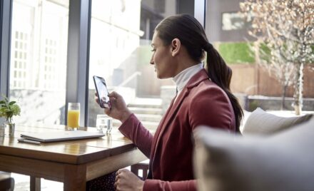 Female small business executive at table on using Microsoft Teams on an iPhone.