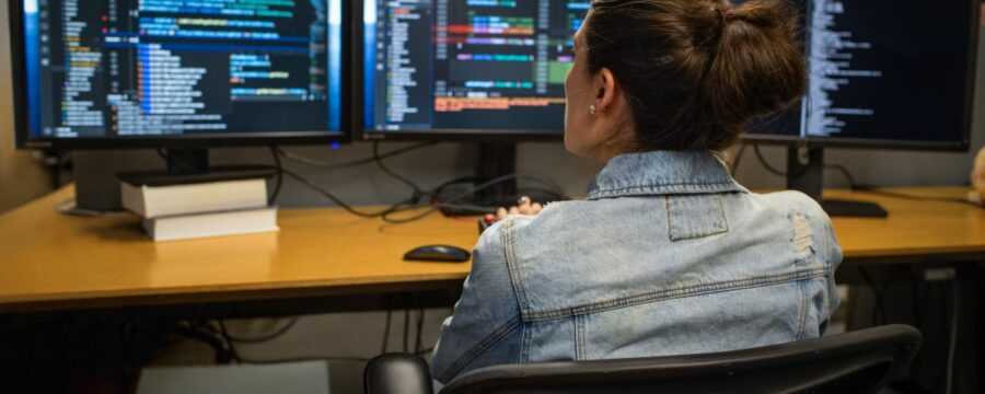 Female developer coding her workspace in an enterprise office, using Visual Studio on a multi-monitor set up.