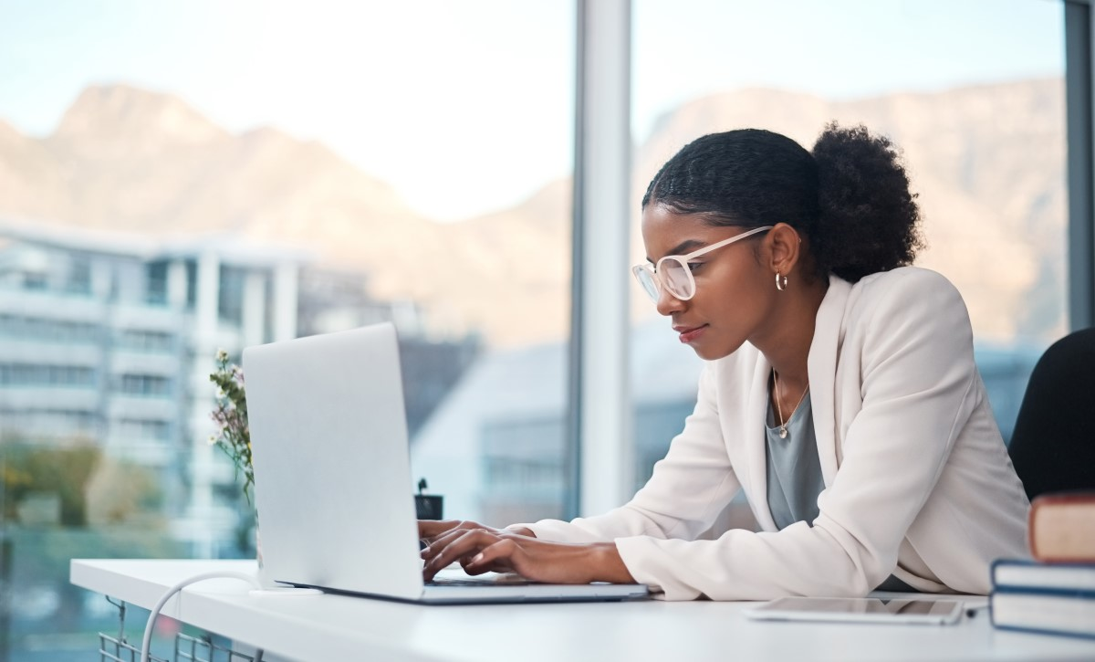 Shot of a young businesswoman using a laptop at her desk in a modern office.